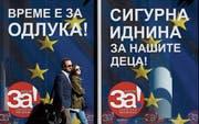 Passanten vor einem Kampagnen-Plakat in Skopje. (Bild: Boris Grdanoski/AP (27. September 2018)