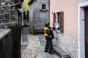 Um solche Dienstleistungen fürchtet die SP: Eine Pöstlerin übergibt einer Kundin ihre Briefe durchs Fenster. Bild: Samuel Golay/Keystone