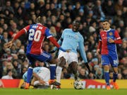 Manchester City's Yaya Toure, center, challenges for the ball with Basel's Geoffroy Serey Die, left, during the Champions League, round of 16, second leg soccer match between Manchester City and Basel at the Etihad Stadium in Manchester, England, Wednesday, March 7, 2018. (AP Photo/Rui Vieira)