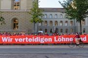 """Menschen demonstrieren waehrend der Aktion von Arbeitnehmenden zum Arbeitnehmerrecht """"Rote Linie Arbeitnehmerrechte"""", am Mittwoch, 5. September 2018 vor dem Bundeshaus in Bern. (KEYSTONE/Anthony Anex)"""