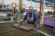 Ein Mitarbeiter der Arbonia-Produktion prüft einen Heizkörper auf Lecks. Bild: Gaëtan Bally/Keystone (Arbon)