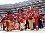 American-Football-Star Colin Kaepernick (Bildmitte) ging vor zwei Jahren während der amerikanischen Hymne auf die Knie und zog so den Zorn von US-Präsident Trump auf sich. (Bild: KEYSTONE/AP/MARCIO JOSE SANCHEZ)