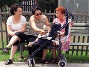 Die Generationensolidarität in der Schweiz spielt: Frauen verschiedenen Alters kümmern sich um ein Kind im Buggy. (Bild: KEYSTONE/MARTIN RUETSCHI)