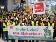 Mitglieder der Gewerkschaft Verdi stehen am Flughafen Köln mit Fahnen und einem Transparent. (Bild: Keystone/DPA/FEDERICO GAMBARINI)