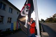 Alan Germann, Präsident des Häggenschwiler Schulrats, posiert mit einer Totenkopf-Flagge vor dem Oberstufenschulhaus Rietwies. (Bild: Urs Jaudas, 28. März 2011)