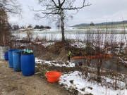 Feuerwehrangehörige errichten eine Ölsperre in der Bünz. (Bild: Kantonspolizei Aargau)