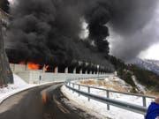 Aus dem Schallbergtunnel oberhalb von Ried-Brig dringen nach einem Carbrand Flammen und Rauch. (Bild: Kantonspolizei Wallis)