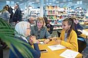 Die 16-jährige Lulya Araya (gelber Pulli) weiht Inge Thomi (links) und Margrith Lanninger in die Geheimnisse ihres Smartphones ein. (Bild: Maria Schmid (Zug, 12. Januar 2019))