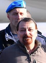 Ein Polizist eskortiert Cesare Battisti bei seiner Ankunft im Flughafen in Rom. Bild: Ettore Ferrari/EPA (Rom, 14. Januar 2019)