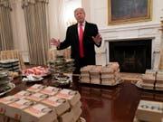 Pizza, Hamburger und Pommes anstelle feiner Häppchen: Wegen der Haushaltssperre hat US-Präsident Donald Trump ein Hochschul-Football-Team im Weissen Haus mit Fastfood bewirtet. (Bild: Chris Kleponis / EPA, Washington, 14. Januar 2019)