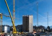 Das Solitaire-Hochhaus im Horwer Zentrum steht bereits, noch ist es aber verhüllt. Derweil kündigen Bauprofile auf dem Nachbargrundstück schon das nächste, ebenfalls 14-stöckige Hochhaus an. (Bild: Eveline Beerkircher (Horw, 16. Januar 2019))