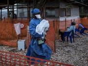 Eingesundheitsmitarbeiter bringt ein vier Tage altes Baby, das wahrscheinlich an Ebola erkrankt ist, in ein Behandlungszentrum. (Bild: KEYSTONE/AP Medecins Sans Frontieres/JOHN WESSELS)