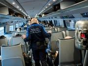 Mitarbeiter der Grenzwache kontrollieren in einem Zug Passagiere. (Bild: KEYSTONE/TI-PRESS/GABRIELE PUTZU)