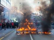 Brennendes Kartenhaus an der unbewilligten Anti-WEF-Kundgebung am Samstag in Berns Innenstadt. (Bild: Keystone/PETER KLAUNZER)