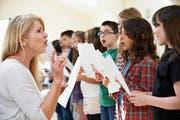 Eine Lehrerin singt mit Kindern: In Ostschweizer Schulen ertönt die Landeshymne nur selten. (Bild: Getty)