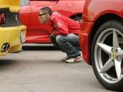 Mit Liebe für's Detail: Ein Fan begutachtet den legendären Sportwagen aus Maranello. (Bild: KEYSTONE/AP/WALLY SANTANA)