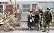 So sah der Alltag 1972 aus: Britische Truppen helfen einer Zivilistin um eine Barrikade herum. (Bild: AP)