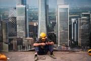 Ein chinesischer Bauarbeiter surft in einer Pause mit seinem Smartphone. (Bild: Andy Wong/AP, Peking, 19. September 2018)