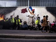 Mit seinem Wandgemälde, das Eugène Delacroix' Werk «Die Freiheit führt das Volk» nachempfunden ist, solidarisiert sich der Künstler Pascal Boyart in Paris mit der Bewegung der Gelbwesten. (Bild: Keystone/EPA/ETIENNE LAURENT)