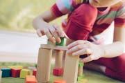 Ein Kind spielt in einer Tagesstätte mit Klötzchen. (Bild: Getty)