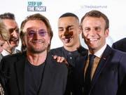 Der französische Präsident Macron (rechts) mit dem irischen U2-Sänger Bono (2. von links) in Lyon. (Bild: KEYSTONE/AP AFP Pool/LUDOVIC MARIN)