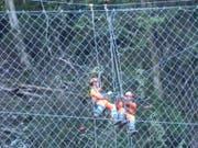 Arbeiter stellen das Steinschlagschutznetz am Axen in Stand. (Bild: Bundesamt für Strassen Astra)