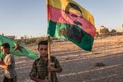 Ein kurdischer Junge demonstriert mit einer Fahne des Kurdenführers Abdullah Öcalan für mehr Selbstbestimmung. (Bild: Imago Images)