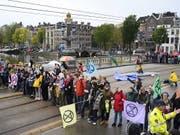 Aktivisten der Umweltbewegung Extinction Rebellion haben am Samstag in Amsterdam eine Brücke blockiert. (Bild: KEYSTONE/EPA ANP/EVERT ELZINGA)