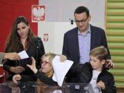 Polens Ministerpräsident Mateusz Morawiecki mit Familie am Sonntag bei der Stimmabgabe - die Regierungspartei Recht und Gerechtigkeit (PiS) von Morawiecki errang bei der Parlamentswahl ersten Prognosen zufolge einen klaren Sieg. (Bild: Keystone/EPA PAP/PAWEL SUPERNAK)