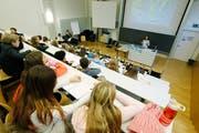 Kinder sitzen im Hörsaal der PH Zug und hören den Ausführungen der Désirée Berhane-Gygax vom Verein Therapiehunde Schweiz zu. (Bild: Stefan Kaiser, Zug, 22. November 2017)