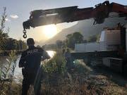 Walliser Kantonspolizisten bei der Bergung des Autowracks aus der Rhone. Nun steht fest, dass im Auto ein Mann und ein Mädchen gesessen hatten, die seit einem Unwetter vermisst werden. (Bild: KEYSTONE/KANTONSPOLIZEI WALLIS)