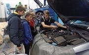 Ein Mitarbeiter erklärt, wo welche Teile im Motor zu finden sind. (Bild: Paul Gwerder, Schattdorf, 14. Oktober 2019)
