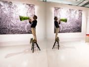 Ein Mann übt mit Flüstertüte im Ehrengast-Pavillon auf der Buchmesse für eine bevorstehende Performance. Der Raum wurde mit Spiegelflächen optisch erweitert und wirkt licht, kühl, minimalistisch. (Bild: Keystone/DPA/ANDREAS ARNOLD)