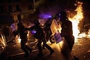 Polizisten zwischen brennenden Barikaden. (Bild: AP, Barcelona, 16. Oktober 2019)