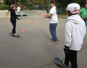 Geschicklichkeitsübung: Auf dem Rollbrett fahrend den Frisbee fangen und wieder zurückwerfen.