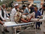 Sanitäter kümmern sich um einen der Dutzenden Verletzten nach dem Bombenanschlag auf eine Moschee in der ostafghanischen Provinz Nangarhar. (Bild: KEYSTONE/AP/WALI SABAWOON)