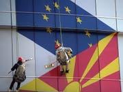 Arbeiter putzen die Fassade am EU-Büro in Skopje: Aufgemalt sind die Flaggen der EU und Nordmazedoniens. (Bild: KEYSTONE/EPA/NAKE BATEV)