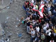 Anti-Regierungs-Demonstranten versuchen in Beirut Stacheldraht zu überwinden und zum Regierungspalast vorzudringen. (Bild: KEYSTONE/AP/HASSAN AMMAR)