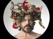 Für Koen Vanmechelen durchdringt das Huhn alle künstlerischen Formen und Dimensionen: Der belgische Künstler mit seinem Kopfschmuck aus Schlangen und Hühnerköpfen. (Bild: Handout: Teatro dell'architettura)