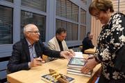 Peter Bolli und Ernest Menolfi signieren an der Vernissage in der Mehrzweckhalle Hauptwil ihr Buch. (Bild: Yvonne Aldrovandi-Schläpfer)