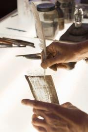 Der Glasmaler zeichnet mit dem Federkiel.