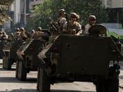 Nach erneuten schweren Ausschreitungen und Brandanschlägen auf U-Bahnstationen patrouilliert am Samstag das chilenische Militär in den Strassen der Hauptstadt Santiago. (Bild: KEYSTONE/AP/ESTEBAN FELIX)