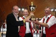 Martin Sebastian von Alpenrosen überreicht Präsident Karl Thoma und Dirigent Rolf Gmür (v.l.) den Pokal als Preis für die beliebteste Blaskapelle der Schweiz. (Bild: Trudi Krieg)