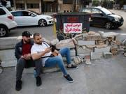 Mit Sitzstreiks, Barrikaden und quergestellten Fahrzeugen blickieren Demonstranten im Libanon wichtige Verkehrsadern. (Bild: KEYSTONE/AP/HUSSEIN MALLA)