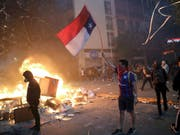 In Chile gab es am Montag (Ortszeit) erneut vielerorts Ausschreitungen - in der Hauptstadt Santiago geriet sogar ein Einkaufszentrum in Brand. (Bild: KEYSTONE/AP/RODRIGO ABD)