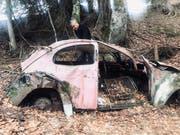 Uli Mack begutachtet das VW-Brezelkäfer-Wrack im Bündner Wald. (Bild: PD)