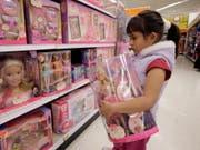 Kundin in einem US-Geschäft vor Regalen mit Puppen des «Barbie»-Herstellers Mattel. (Bild: KEYSTONE/AP/NICK UT)