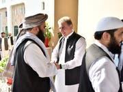 Händeschütteln und Umarmungen für die Taliban: Pakistans Aussenminister Shah Mehmood Qureshi (Mitte) beim Begrüssen der Delegation in Islamabad. (Bild: KEYSTONE/AP Pakistan Foreign Office)
