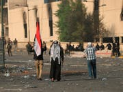 Frustration über Korruption und Stillstand: Irakische Sicherheitskräfte riegeln die Grüne Zone in Bagdad ab, während im Vordergrung Zivilisten demonstrieren. (Bild: KEYSTONE/AP/HADI MIZBAN)