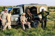 Im Masai Mara Nationalpark: Simon Seiler, Dominic Kast, Chef Mathew Mutinda (in der Mitte mit Hut) und Kollegen von Kenya Wildlife Services. (Bild: SRF)